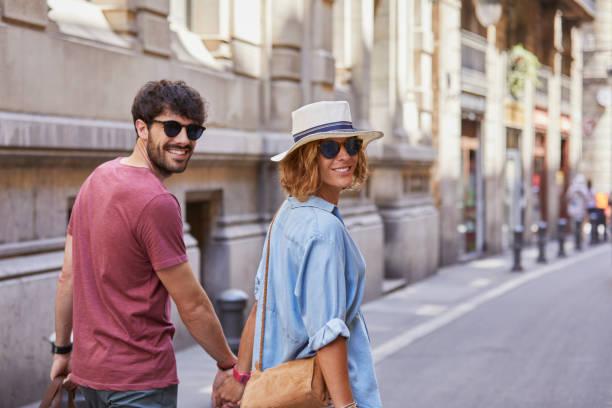 Couple de voyageurs qui porte des lunettes de soleil, un chapeau et un sac à bandoulière